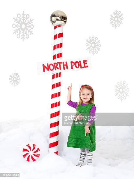 Little girl (18-23 months) standing next to North Pole sign