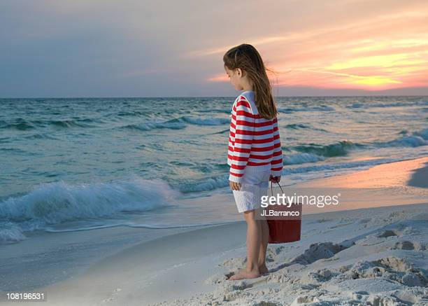 little girl standing on beach at sunset - destin beach stock pictures, royalty-free photos & images