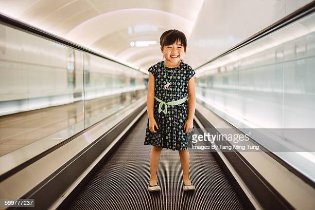 Little girl standing on escalator smiling joyfully