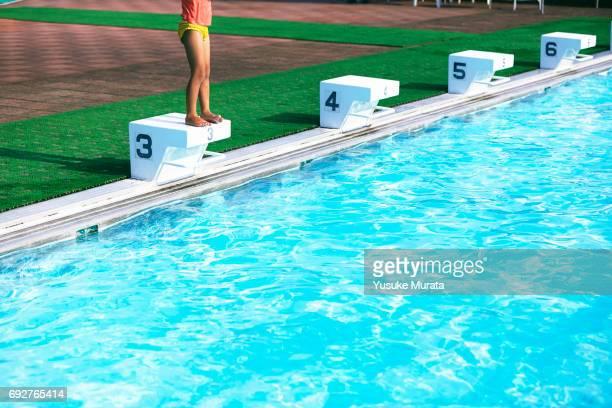 Little girl standing on springboard beside pool