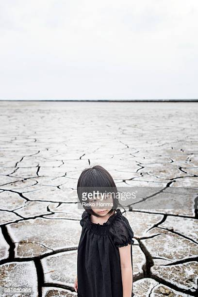 Little girl standing on the dry land