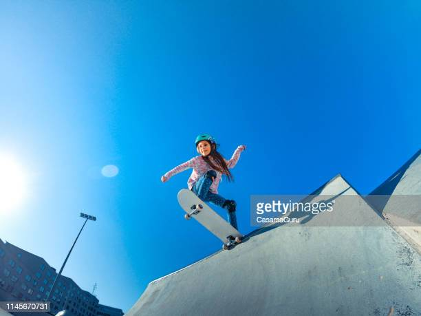 little girl standing on the edge of the skatepark ramp - skating stock pictures, royalty-free photos & images