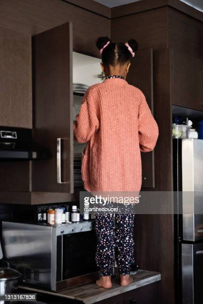 """little girl standing on the kitchen cupboard serving herself. - """"martine doucet"""" or martinedoucet stock pictures, royalty-free photos & images"""