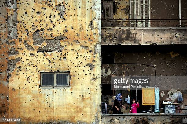 A little girl standing on the terrace of a house riddled by the shells Many buildings of the capital city bear the marks from the 15 years civil war...