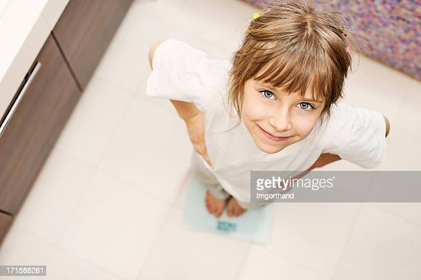 Little girl standing on weight scales