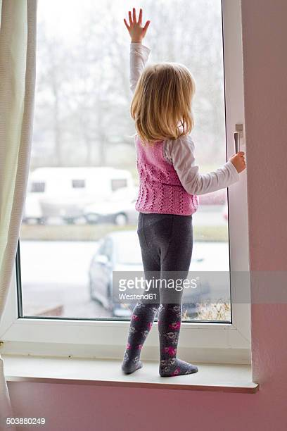 Little girl standing on window sill looking out of window
