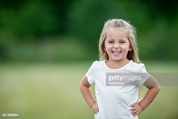 little girl standing outside at the park - maglietta foto e immagini stock
