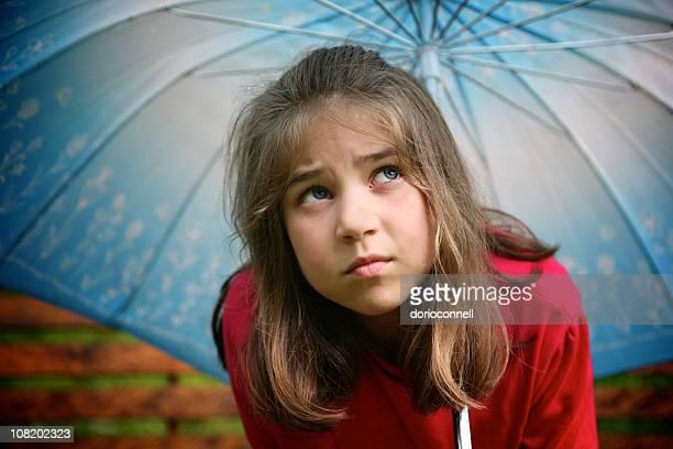 Little Girl Standing Under Blue Umbrella