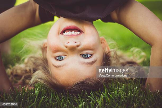little girl standing upside down. - spelen stockfoto's en -beelden