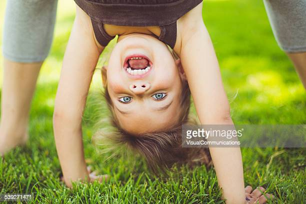 Little girl standing upside down.