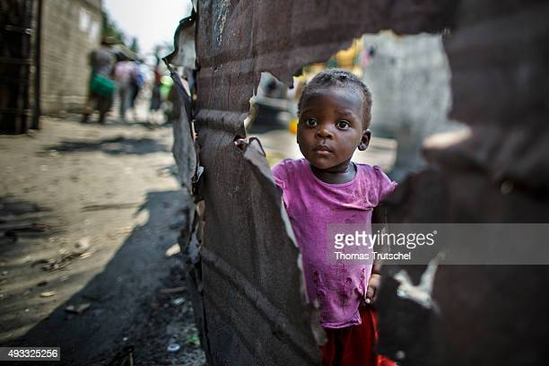 A little girl stands behind a broken wall in a slum in the urban area of Beira on September 28 2015 in Beira Mozambik