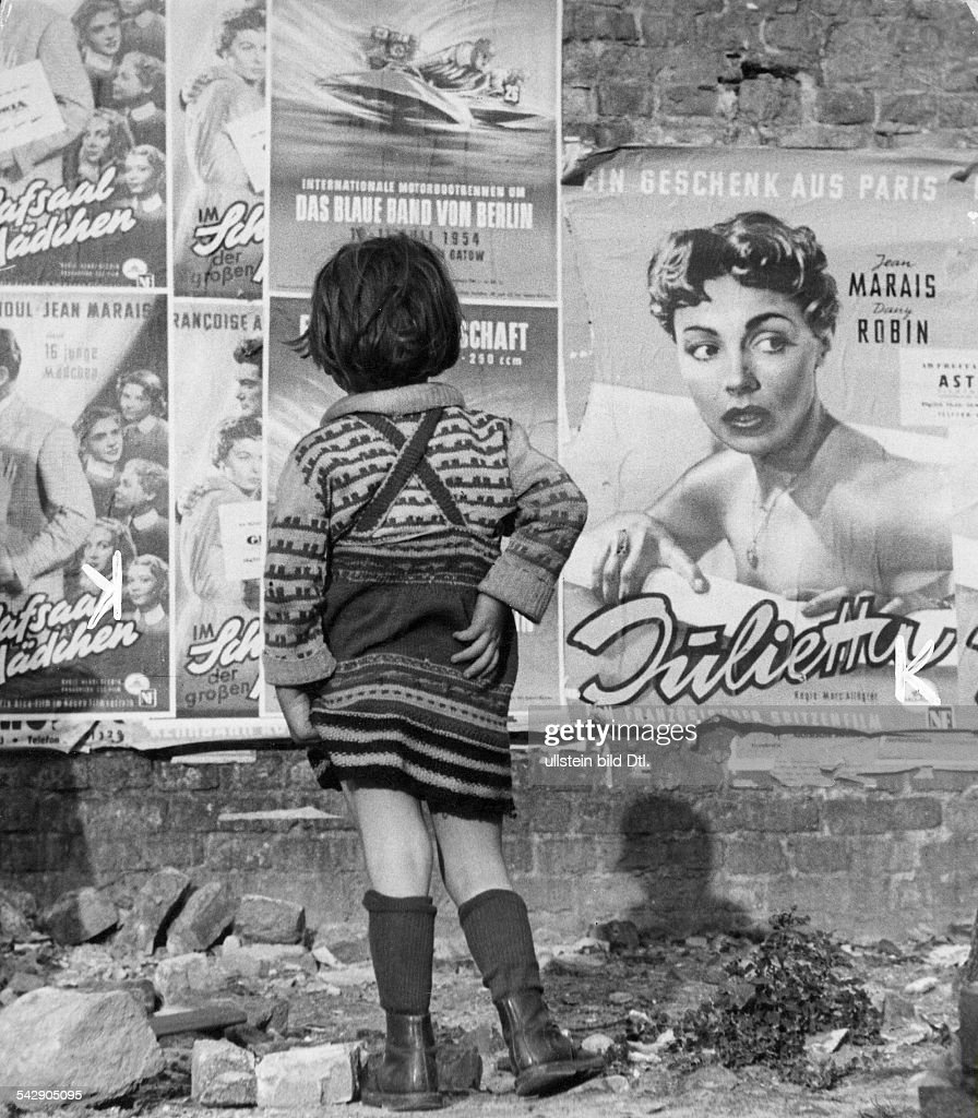 A little girl stands in front of a wall pasted with movie