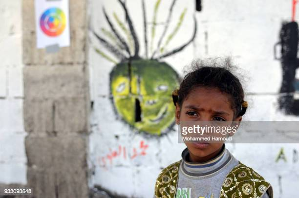 Little girl stands in ftont of graffiti drew during an Open Day of graffiti campaign call for peace on March 15, 2018 in Sana'a, Yemen.