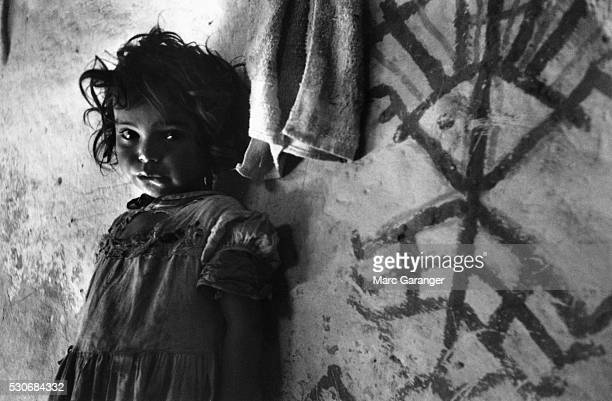 A little girl stands next to a mystical symbol on the wall of her home that is meant to ward off evil spirits