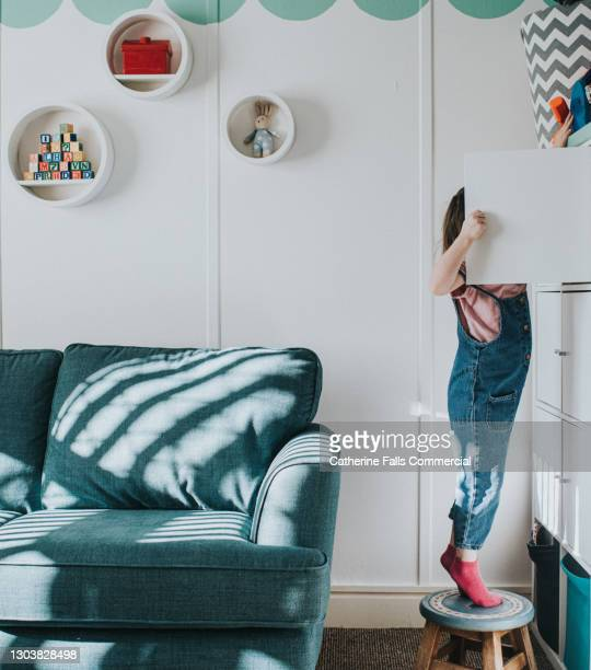 a little girl stands on her tip-toes on a little stool to open a cabinet that is too high to reach otherwise - innovation stock pictures, royalty-free photos & images