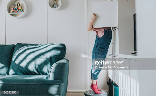 a little girl stands on her tip-toes on a little stool to open a cabinet that is too high to reach otherwise - limb body part stock pictures, royalty-free photos & images
