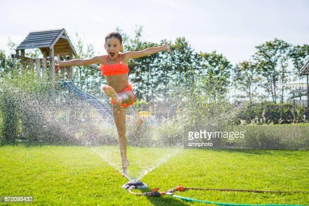 little girl step jump over garden sprinkler