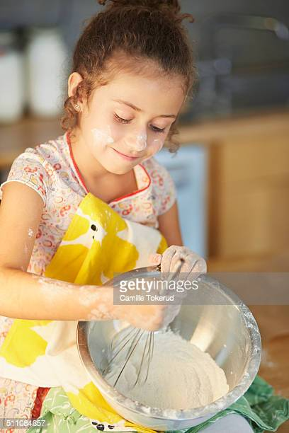 Little girl stirring ingredients for cake