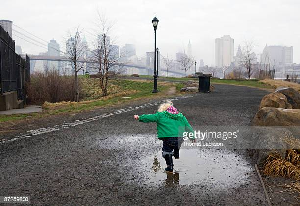 Little girl stomping in puddle