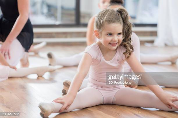 little girl stretches her legs in ballet class - little girls dressed up wearing pantyhose stock photos and pictures