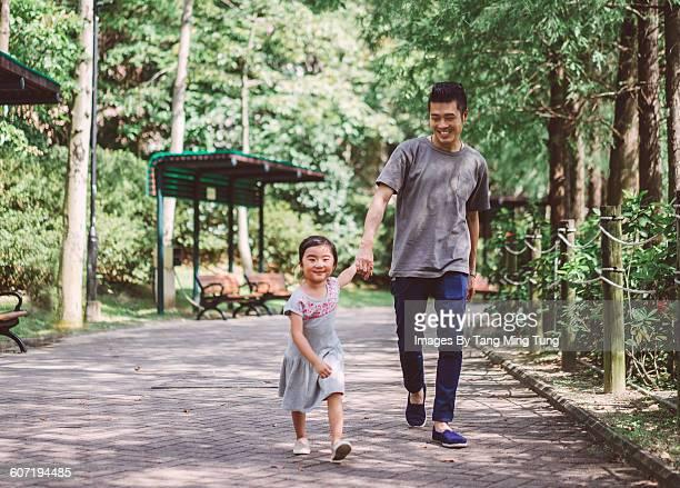 Little girl strolling in park with dad joyfully