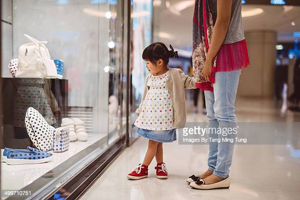 Little girl strolling in shopping mall with mom