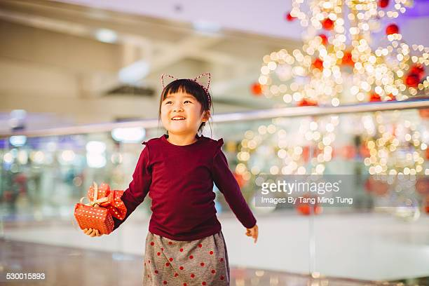Little girl strolling joyfully with gift in mall