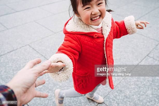 Little girl strolling with dad joyfully in park