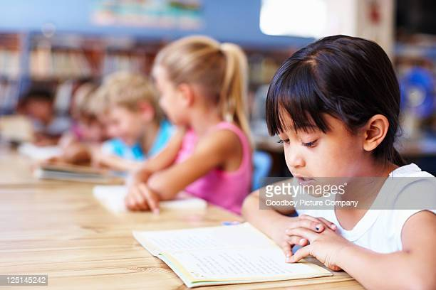 Little girl studying in the library with friends