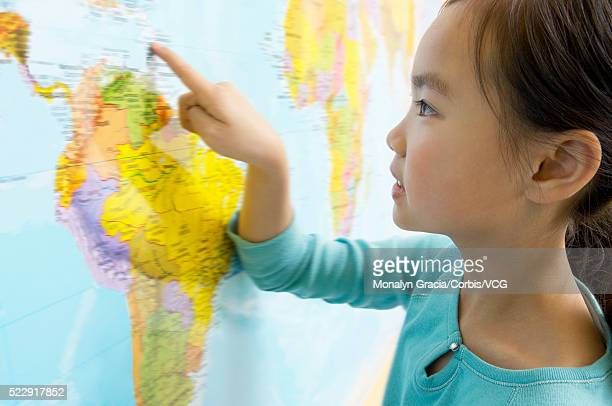 Little girl studying world map