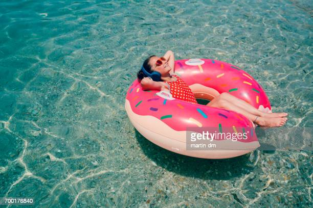 little girl sunbathing in life preserver - effortless stock pictures, royalty-free photos & images
