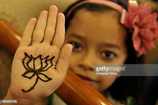 A little girl supporter of of Bhartiya Janta Party showing her hand decorated with henna with the party symbol as she campaigns in favour of BJP...