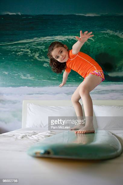 Little girl surfing on bed
