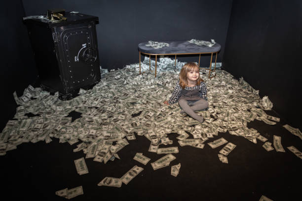 Little girl surrounded with money bills while sitting on floor.