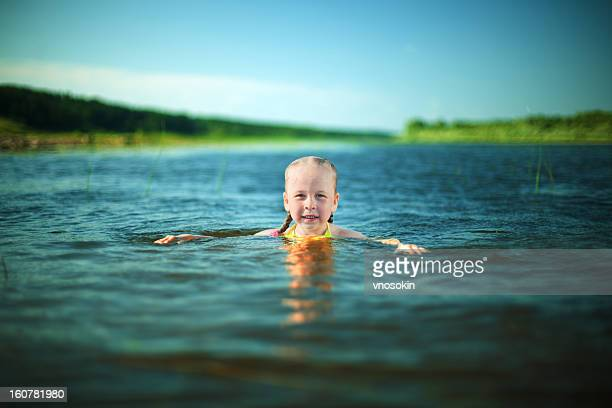 Little girl swimming on river