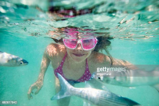 Little girl swimming underwater in sea among fish