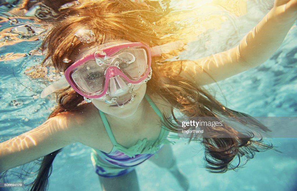 Little girl swimming underwater : Stock Photo
