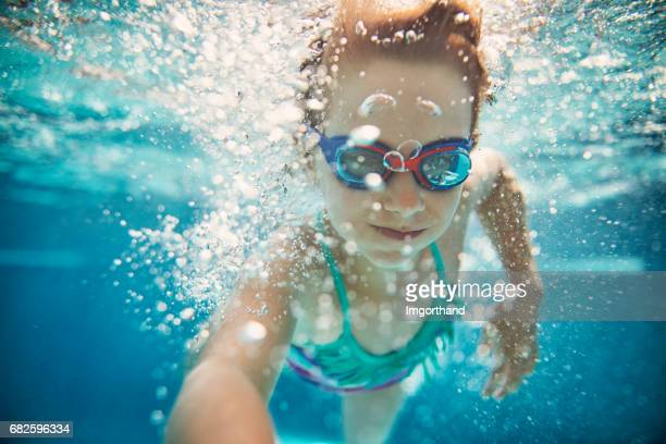 Little girl swimming underwater.