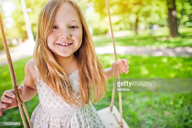 Little girl swinging in a park