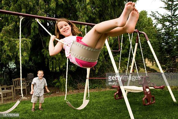Little girl swinging in her backyard with younger brother Playing