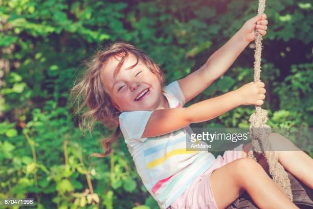 Little girl swinging in summer