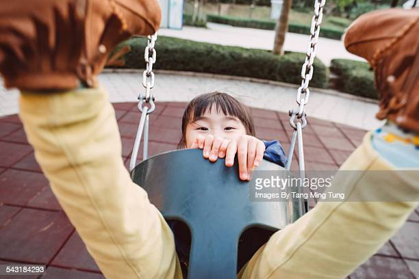 Little girl swinging joyfully on swing