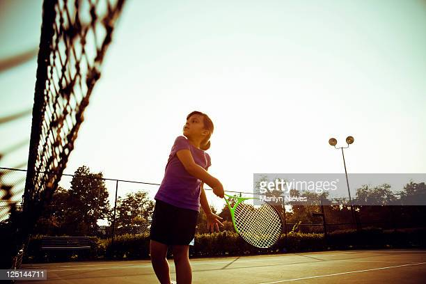 little girl swinging on tennis court
