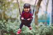 Little girl swinging on the swing joyfully