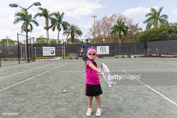 Little Girl Swings Her Tennis Racquet on the Court