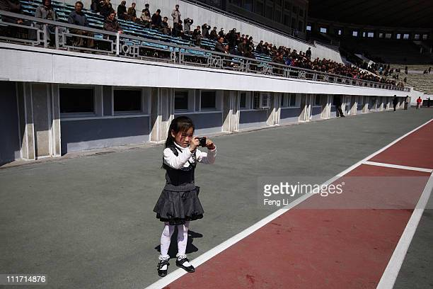 A little girl take photos during a football match between women grassroots teams at Kim Il Sung Stadium on April 3 2011 in Pyongyang North Korea...