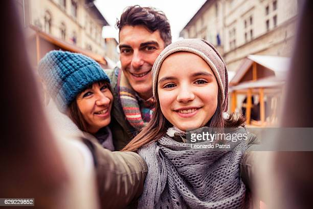 Little girl takes a selfie with parents in Christmas Markets
