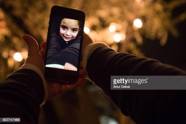 Little girl taking a selfie with smartphone with the christmas lights at home.