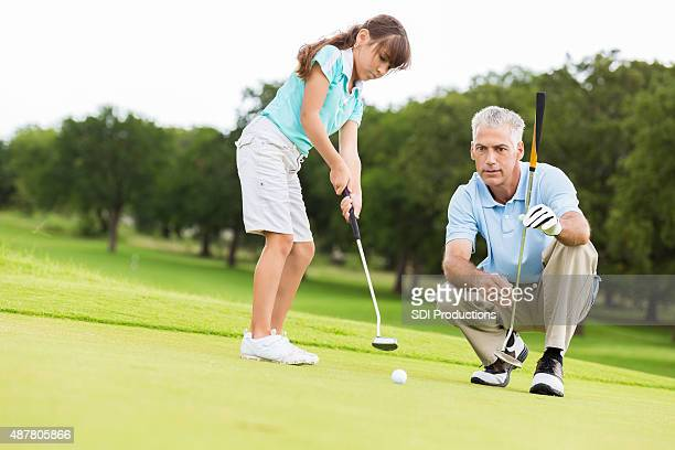 Little girl taking golf lesson from country club pro
