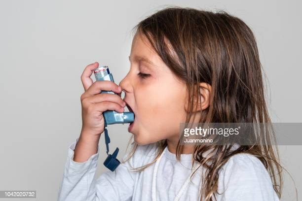 little girl taking her asthma medicine - asthma stock pictures, royalty-free photos & images